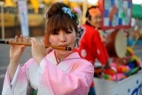 A_young_Japanese_girl_in_traditional_outfit_playingg_flute_during_festival._Fukuoka,_Japan,_East_Asia.jpg